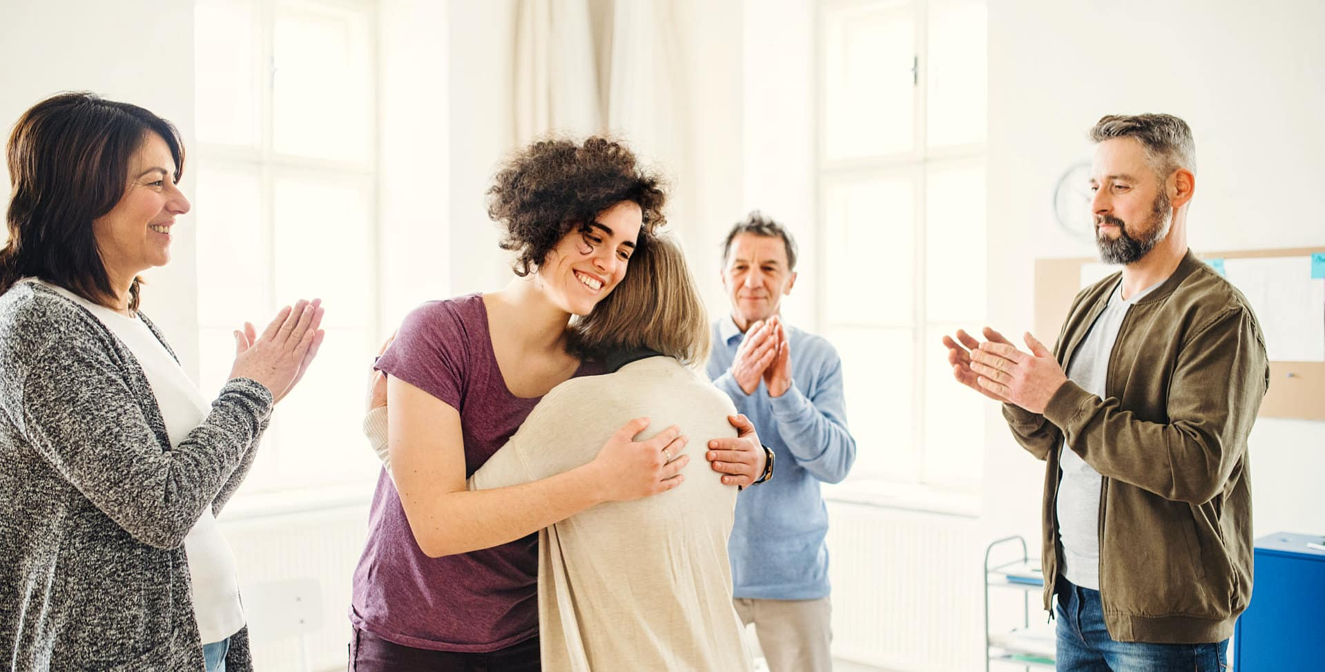 female psychologist hugging the senior woman while the group of people are clupping their hands