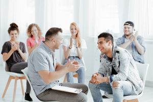 psychologist and his patients laughing during group session for troubled teenagers