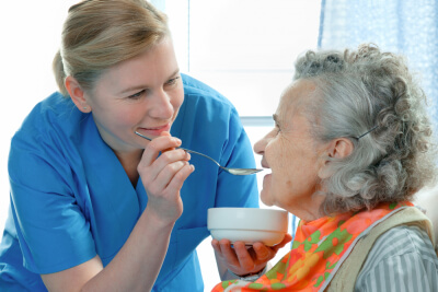 caregiver fed healthy meal to senior woman